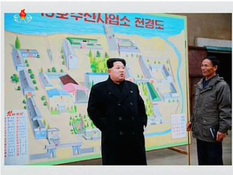 Kim Jong-un standing front of a stylized drawing of Fishery Station No. 15 prior to its modernization program began. Although this drawing does not show the small compound and old per to the northeast, satellite imagery clearly shows their use by the fishery station, (Rodong Sinmun, November 25, 2015).