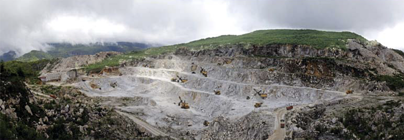 Surface mining (Foreign Trade, 2018.01.01).png. Surface mining operations reportedly in the area of the Ryongyang Mine. A propaganda image showing approximately eight shoves and numerous mine dump trucks.