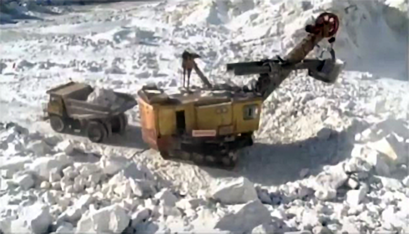 Surface shovel (KCTV, 2018.08.15).png. A shovel and mine dump truck excavating ore, reportedly in the area of the Ryongyang Mine.